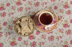 En kopp te och ett tefat med läcker halva Royaltyfri Fotografi