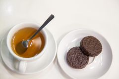 En kopp te och kakor på tabellen i vit bakgrund arkivbild