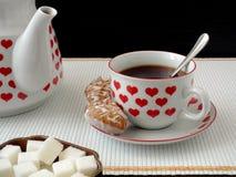En kopp te och en tekanna med en hjärtabild arkivbilder