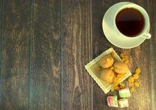 En kopp te på ett tefat, tre valnötter, vita russin och turkisk fröjd på en textilservett, lögn på en trätabell 1 livstid fortfar arkivbilder