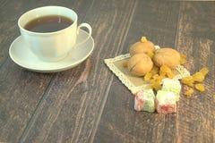 En kopp te på ett tefat, tre valnötter, vita russin och turkisk fröjd på en textilservett, lögn på en trätabell 1 livstid fortfar royaltyfri bild