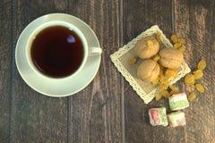 En kopp te på ett tefat, tre valnötter, vita russin och turkisk fröjd på en textilservett, lögn på en trätabell 1 livstid fortfar royaltyfri foto