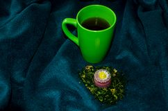 En kopp te på en pläd och en stearinljus royaltyfria bilder