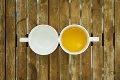 En kopp te & tömmer koppen på trätabellen Royaltyfria Foton