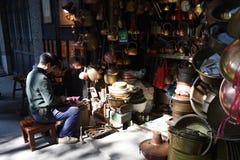 En kopparslagare bygger en brons av hans egen kopparslagare shoppar framme royaltyfri fotografi