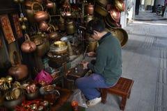 En kopparslagare bygger en brons av hans egen kopparslagare shoppar framme royaltyfria bilder