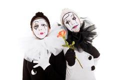 Två clowner, en ger en blomma till annan royaltyfri fotografi