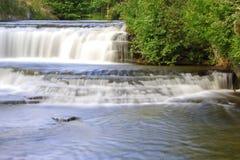 Vattenfallet krediterar på floden Royaltyfri Bild