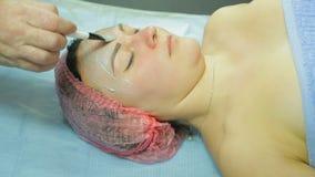 En kosmetolog i handskar sätter en kosmetisk maskering på en framsida för kvinna s Slapp fokus stock video