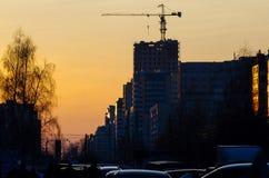 En kran över en konstruktionsplats för nytt hus i staden på solnedgången Arkivfoton