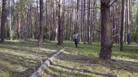 En krigare med en kal torso och en kniv i hans händer kör mycket snabbt till och med skogen som kameran skjuter i långsam mo film stock video