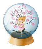 En kristallkula med en fe och ett träd för körsbärsröd blomning Royaltyfri Fotografi