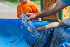 En kristen familj som häller det heliga vattnet i en flaska från den heliga våren royaltyfria foton