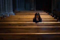 En kristen flicka är sitta och be med bruten hjärta i royaltyfri bild