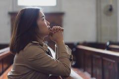 En kristen flicka är sitta och be med bruten hjärta i arkivfoton