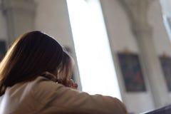 En kristen flicka är sitta och be med bruten hjärta i royaltyfri foto