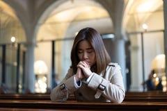En kristen flicka är sitta och be med bruten hjärta i royaltyfria bilder