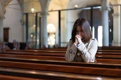 En kristen flicka är sitta och be med bruten hjärta i arkivbilder