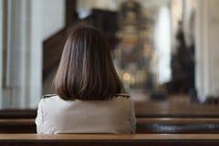 En kristen flicka är sitta och be med bruten hjärta i royaltyfria foton