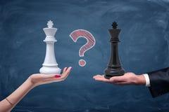 En kritafrågefläck mellan en kvinnlig hand med en vit schackkonung och en manlig hand med en svart konung Arkivbilder