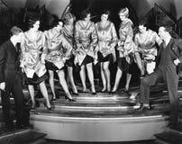 En körlinje av kvinnor som av visar deras ben till två män (alla visade personer inte är längre uppehälle, och inget gods finns S Arkivfoton