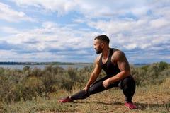 En kroppsbyggare som gör enrad för sträckning av hans ben på en naturlig bakgrund En stilig muskulös man utomhus arkivfoto