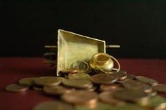 En kruka av guld och en kristallgemstone på lott av pengarmynt arkivbild