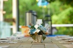 En kruka av pålagda konstgjorda blommor den dinning tabellen Arkivfoton