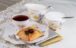 En kruka av te och kakan på porslinbordsservis Arkivfoton
