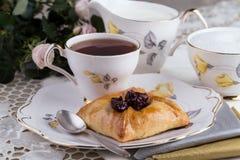 En kruka av te och kakan på porslinbordsservis Royaltyfri Bild