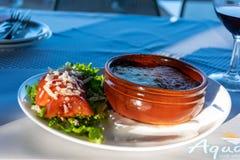 En kruka av varm moussaka på en tabell i ett kafé på stranden i aftonen arkivfoto