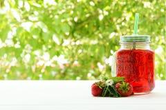 En krus av ny jordgubbefruktsaft på en grön bakgrund Royaltyfri Foto