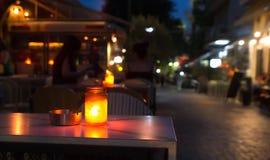 En krus med en stearinljus på en tabell på natten Royaltyfri Fotografi