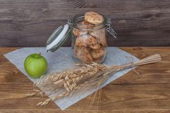En krus med hemlagade kakor och ett äpple på en bakgrund av träbräden royaltyfria foton