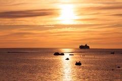 En kryssningship nära segla utmed kusten under solnedgång Royaltyfri Bild