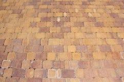 En kulör tegelplatta på en trottoar Arkivfoto