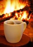 En kupa av hoat kaffe framme av spisen Arkivbild