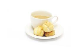 En kupa av kaffe och eclairs Arkivfoton