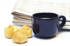 En kupa av kaffe och eclairs mot tidningen Arkivbild