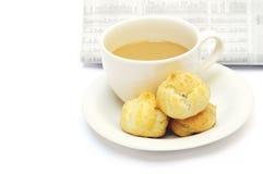 En kupa av kaffe och eclairs mot tidningen Royaltyfri Foto