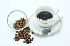 En kupa av kaffe och kaffebönor Royaltyfria Bilder
