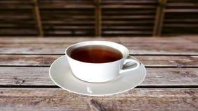En kupa av tea p? ett tr? bordl?gger arkivfilmer