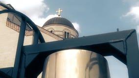 En kupol på den ortodoxa templet med ett kors, en guld- kyrklig klocka arkivfilmer