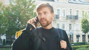 En kurir med en gul påse talar på telefonen med en kund som specificerar leveransadressen Skäggig grabb med a arkivfilmer