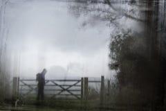 En kuslig kontur av ett ensamt med huva diagram med en ryggsäck vid en port som omges av träd Med ett mörkt spöklikt suddigt abst royaltyfri bild
