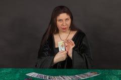 En kvinna är avläsningstarotkort Arkivfoto