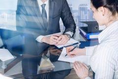 En kvinna är handstillegitimationshandlingar på mötet med en affärsman på ett kontor arkivbild