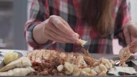 En kvinna äter ivrigt skaldjur med hennes händer på en tabell i ett kafé lager videofilmer