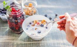 En kvinna äter yoghurt med sädesslag och bär för frukost, royaltyfri bild