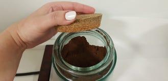 En kvinna öppnar korkräkningen av exponeringsglasbunken med svart kaffe royaltyfri bild